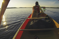 Person and their dog enjoying the lake in a canoe.