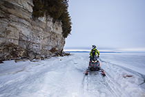 snow mobile on frozen lake next to limestone cliff