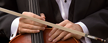 close-up of the hands of a cellist, while holding his instrument